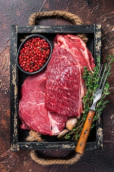 Raw rib eye beef steak in a wooden tray with herbs. dark table. top view.
