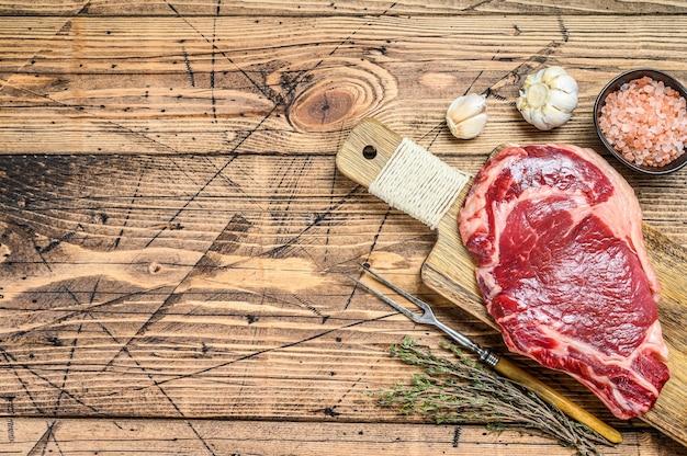 骨付きの生リブアイステーキ。霜降り肉のリブアイ。木製の背景。上面図。スペースをコピーします。