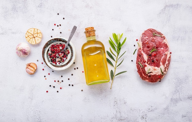 Raw rib eye steak set up  on white concrete background. flat lay of fresh raw beef steak with rosemary and spice on white shabby concrete background top view.