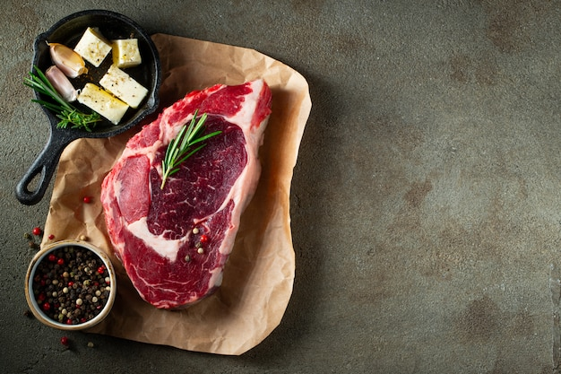 Raw ribeye beef steak with herbs and spices.