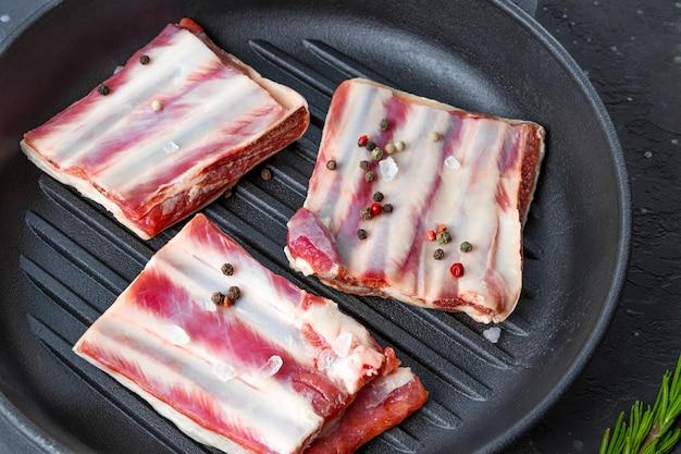 鍋に生のリブ、塩、コショウ、ローズマリーをクローズアップ。高品質の写真