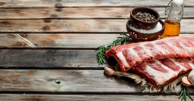 향신료와 로즈마리를 곁들인 생 갈비. 나무 테이블에.