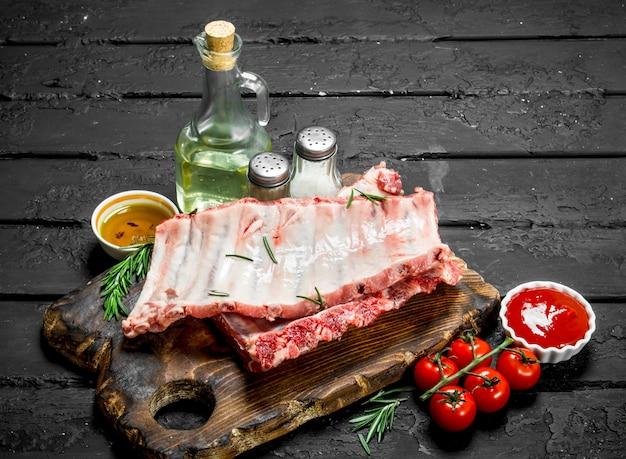 검은 시골 풍 테이블에 향신료와 소스와 함께 원시 갈비.
