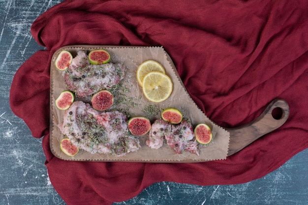 Raw ribs in wooden board with figs, dried herbs and red cloth.