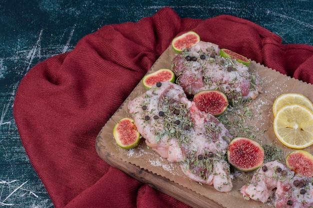 Costolette crude in tavola di legno con fichi, erbe secche e panno rosso.