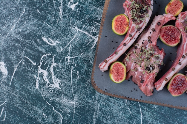 Raw ribs in wooden board with figs and dried herbs.