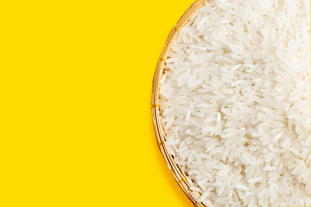 Raw rice in bamboo basket on yellow background.