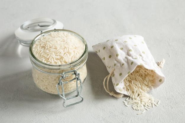 유리 항아리와 회색 콘크리트 배경에 캔버스 가방에 곡물에 원시 쌀 곡물. 곡물 보존 방법. 건강한 유기농식이 식품.