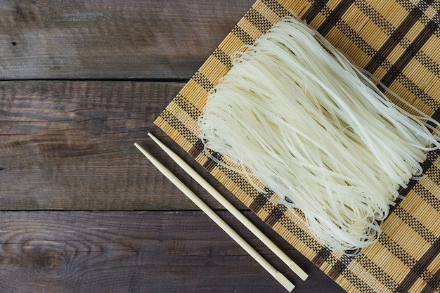 Raw rice noodles in place mat and chopsticks over weathered table