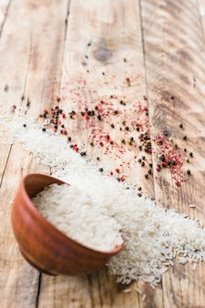 Raw rice spilling out bowl on white surface with black peppers on wooden background