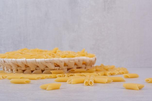 Сырые макароны ригатони в белой миске