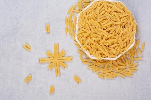 Сырые макароны ригатони в белом шаре.