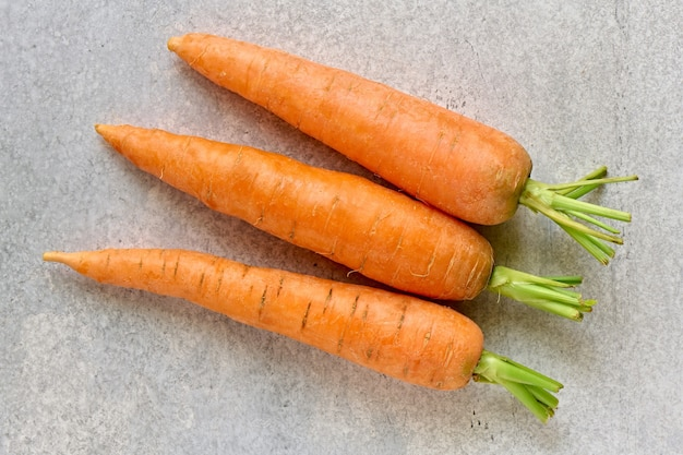 Raw ripe carrot fruit on gray background close up