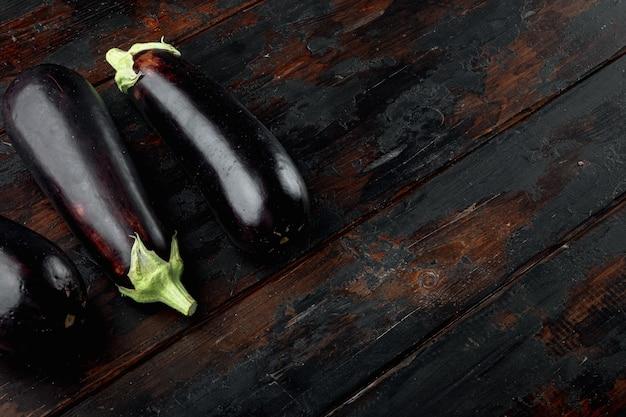 古い暗い木製のテーブルの上に、庭の農場セットからの生の熟したナス