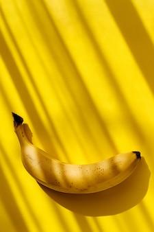 Raw ripe sweet organic one banana on yellow with tropical shadows.