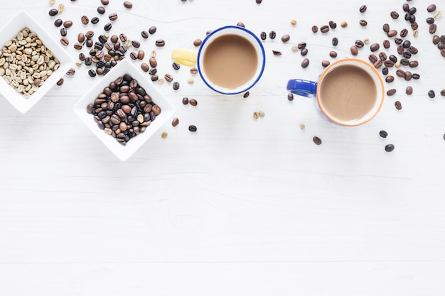 Raw and roasted coffee beans with coffee cup on white wooden background