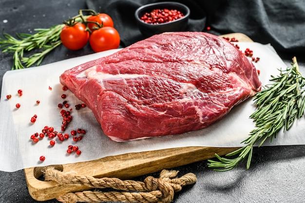 Сырой круглый говяжий вырезать на разделочную доску на черном столе.