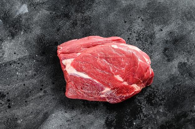 Сырой круглый говяжий вырезать на черном столе.