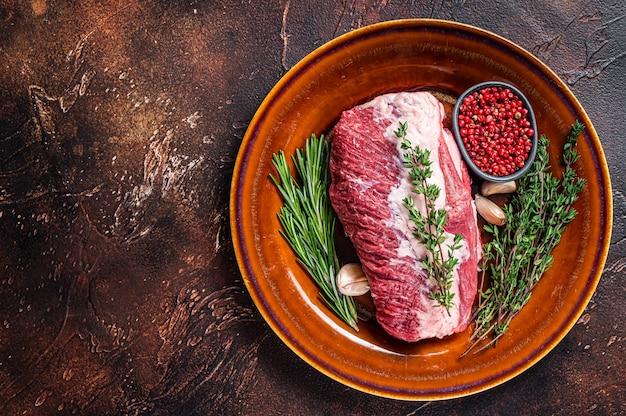 Сырой круглый кусок говядины для жаркого на деревенской тарелке с зеленью. тьма