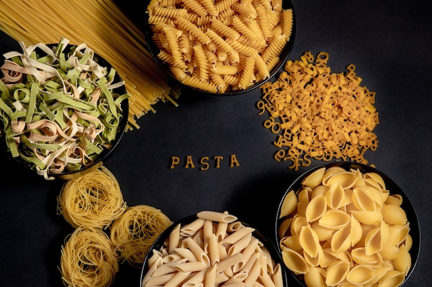 Raw round pasta on a dark background. the word pasta made of wooden letters in the middle. the concept of delicious food. top view, flat lay, copy space.