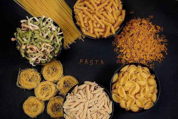 暗い背景に生パスタ。中央に木製の文字で作られたパスタという言葉。おいしい食べ物のコンセプト。トップビュー、フラットレイアウト、コピースペース。