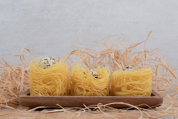 Raw round pasta with quail eggs on marble space.
