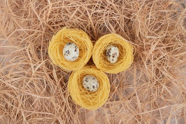 Pasta rotonda cruda con uova di quaglia su spazio di marmo.