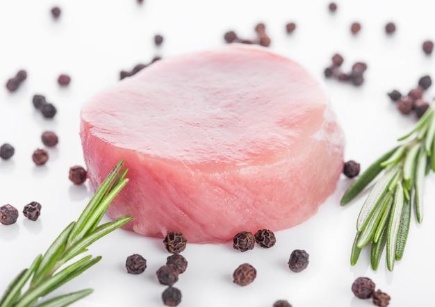 Сырые круглые кусочки стейка из свинины с перцем и розмарином
