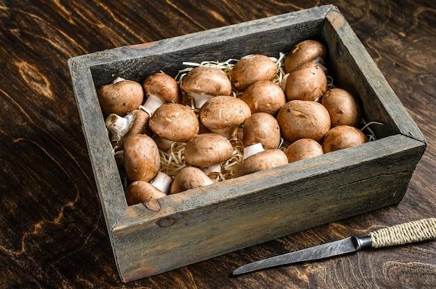 Сырые королевские коричневые шампиньоны в деревянном ящике.