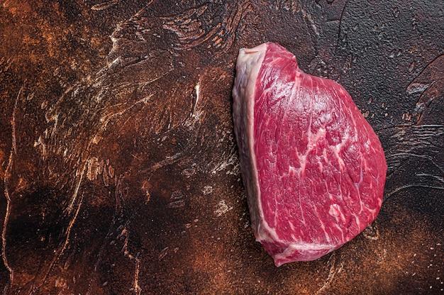 肉屋のテーブルに生のランプビーフカットまたはトップサーロインミートステーキ。上面図。