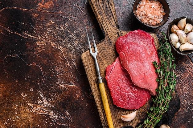 Raw rump beef meat steaks on butcher wooden board