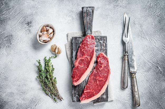 Сырые стейки говядины крупы на деревянной доске с мясным ножом и вилкой. белый фон. вид сверху.
