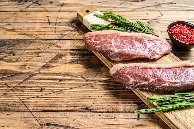 Сырой стейк из огузки на разделочной доске. Premium Фотографии