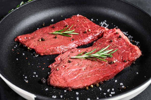 Сырье ромштекс в сковороде. говядина. черный фон. вид сверху