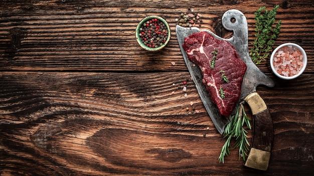 ダークウッドの背景に古い肉切り包丁の生のランプステーキ。バナー、テキストのメニューレシピの場所、上面図。
