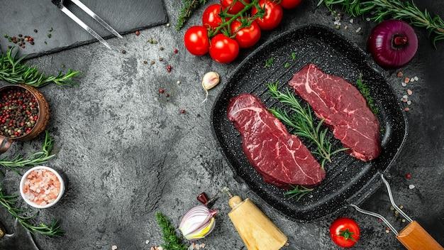 Сырой стейк из крупы на сковороде на темном бетонном фоне со специями, солью и перцем. баннер, место рецепта меню для текста, вид сверху.