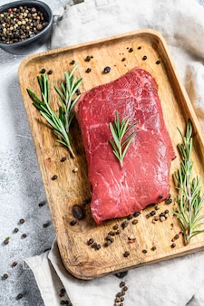 Raw rump steak on a wooden tray. beef meat. gray background. top view.