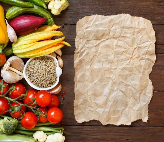 Сырое ржаное зерно в миске и овощи с крафт-бумагой на деревянном столе