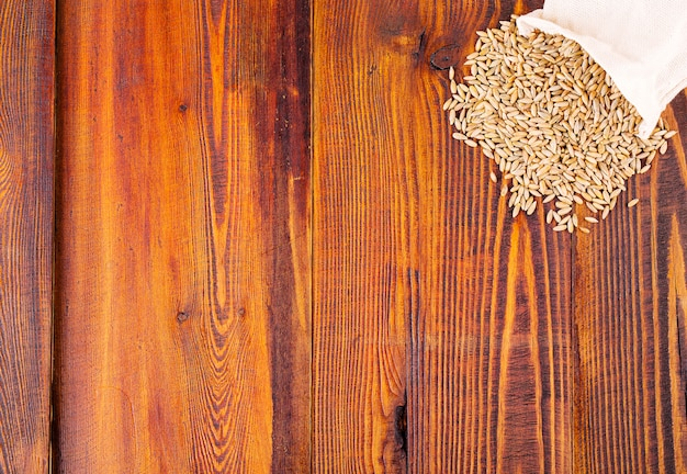 Raw rye on wooden surface background