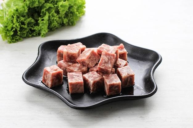 흰색 테이블 위에 배경에 양상추와 스테이크 접시에 원시 saikoro 큐브 쇠고기 스테이크.