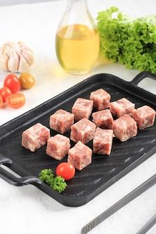 배경에 다른 향신료와 함께 흰색 테이블 위에 배경에 양상추와 스테이크 접시에 원시 saikoro 와규 큐브 쇠고기 스테이크