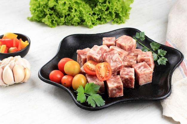 흰색 테이블 위에 배경에 양상추와 함께 스테이크 접시에 원시 saikoro 와규 큐브 쇠고기 스테이크.