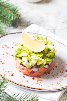 Raw salmon, avocado and purple onion salad. salmon tartar. appetizer for new year's or christmas table