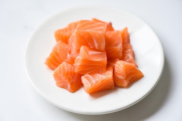 Кубик сырого филе лосося на белой тарелке и белом столе