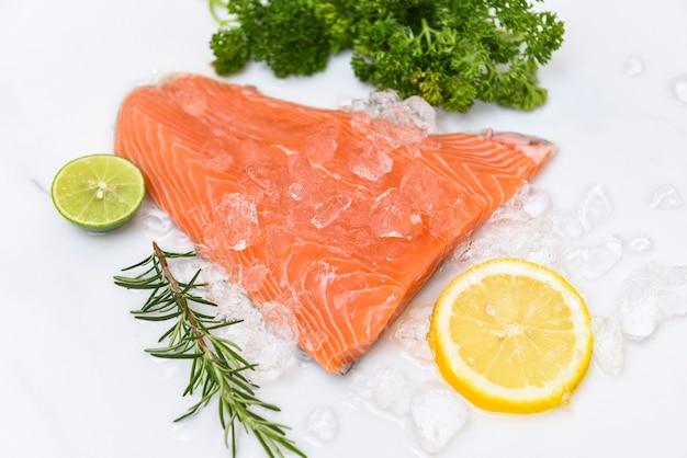 Сырое филе лосося с травами и специями на белом фоне, свежая рыба лосося на льду