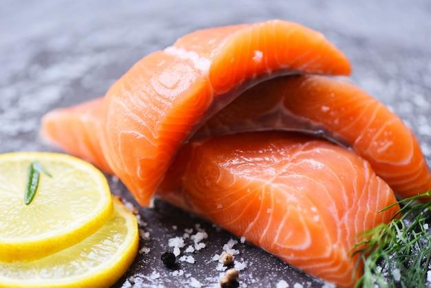 Сырое филе лосося с травами и специями розмарин пищевой лимон на черном