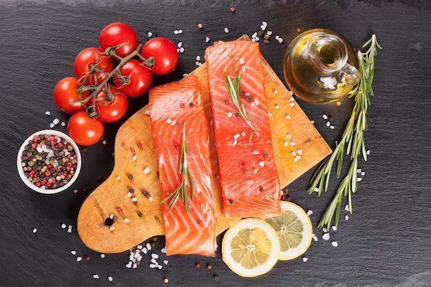 Сырое филе лосося и ингредиенты для приготовления на разделочной доске и фоне темного сланца. вид сверху