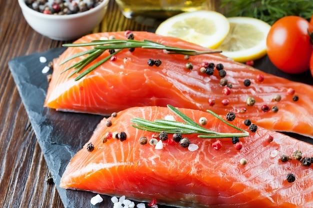 生鮭の切り身とスレイドボードと茶色の木製の背景で調理するための材料。