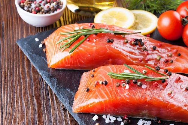 Сырое филе лосося и ингредиенты для приготовления на доске slade и коричневом деревянном фоне.
