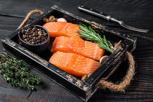 Стейки рыбы филе сырого лосося в деревянном подносе с тимьяном и розмарином. черный деревянный фон. вид сверху.